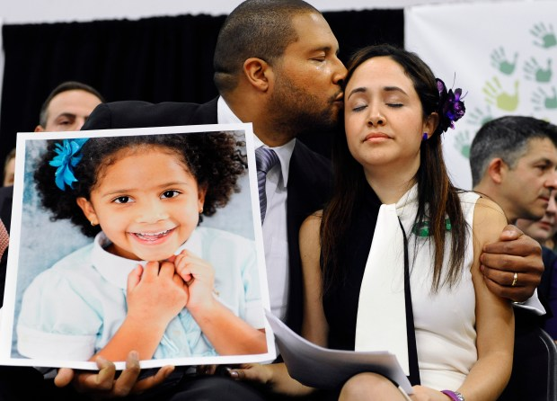 Jimmy Greene, left, kisses his wife Nelba Marquez-Greene while holding a portrait of their daughter, Sandy Hook Elementary School shooting victim Ana Marquez-Greene, in 2013. (AP Photo/Jessica Hill, File)