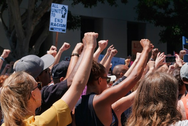 Demonstrators raise clenched fists in defiance to racism during a protest in the Venice beach area of Los Angeles on Saturday, Aug. 19, 2017. Hundreds of people rallied in Southern California to condemn racism in the wake of the deadly events in Charlottesville, Va. (AP Photo/Richard Vogel)