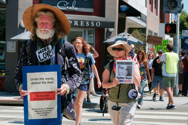David Busch, left, a homeless community organizer is joined by Kris Tibor, carrying a photo in memory of Heather Heyer during protest walk in the Venice beach area of Los Angeles on Saturday, Aug. 19, 2017. Hundreds of people rallied in Southern California to condemn racism in the wake of the deadly events in Charlottesville, Va. (AP Photo/Richard Vogel)