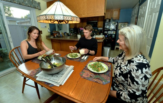 Pat Read, right, and her two children Lisa Read, 30, left, and Jeff Read, 28, have dinner at their home in Danville, Calif., on Wednesday, Aug. 16, 2017. Jeff and Lisa, who both have jobs, moved back into their mother's Danville home a year ago after each were priced out of their apartments in Livermore and Oakland. The three have worked out ground rules about how they live together again, living more like roommates with Lisa and Jeff paying rent. (Doug Duran/Bay Area News Group)