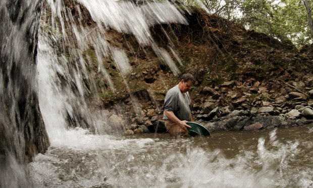 Robert Guardiola of Riverbank pans for gold after collecting graveldeposits under the waterfall on his claim south of Eagle Creek , on May 15, 2017, near Moccasin, Calif. This year's historic rains and runoff are scouring California's rivers and streams, leaving gold fever in the air. (Gina Ferazzi/Los Angeles Times/TNS)