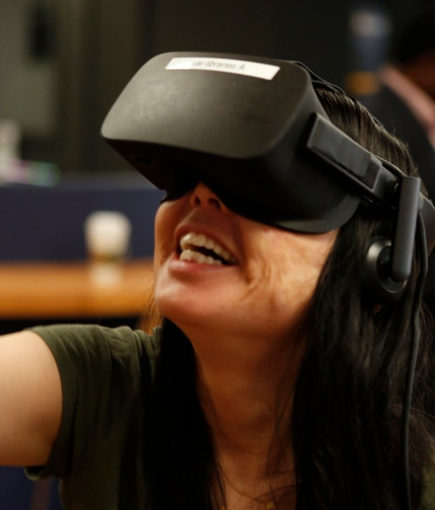 Margaret Yamasaki plays a virtual reality game during a launch of VR headsets through Oculus VRat at Dr. Martin Luther King, Jr. Library's TeenHQ in San Jose, California, Friday, Aug. 11, 2017. Adults and teens got a chance to try the new VR headsets. (Patrick Tehan/Bay Area News Group)