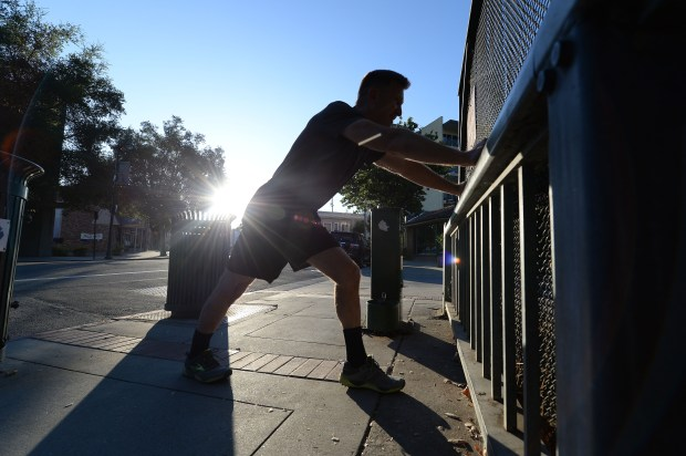 An early morning runner stretches before heading out for a run on the Los Gatos Creek Trail in Los Gatos, Calif., on Thursday, Aug. 31, 2017. Many are getting their workouts in early to avoid the extremely hot weather forecast for later in the day. (Dan Honda/Bay Area News Group)