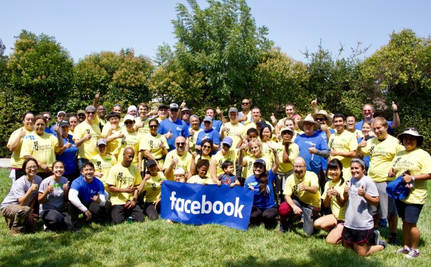 Eighty volunteers, including Facebook employees, gather for a photo during a Block Build event Aug. 19 in the Belle Haven neighborhood of Menlo Park. Facebook and Rebuilding Together Peninsula partnered to rehabilitate three homes in the neighborhood, two on Plumas Avenue and one on Bieber Avenue, in such ways as exterior and interior painting, debris removal, electricity upgrades, grab bar and handrail installation and bathroom and kitchen improvements. (Facebook)