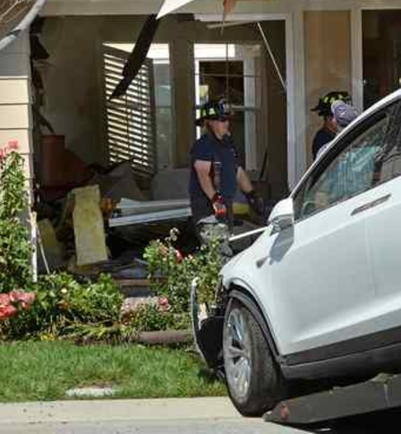 Novato firefighters survey the damage after a car smashed into a home on Woodbridge Way in Novato on Tuesday. (Alan Dep — Marin Independent Journal)
