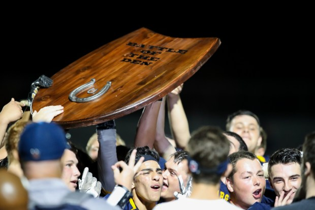 "Leland players hold the ""battle of the den"" trophy high in the air as they celebrate their win. Final score in the ""battle of the den"" rivalry game, Leland 21 / 7 Pioneer(Keith Tharp for Bay Area News Group)"
