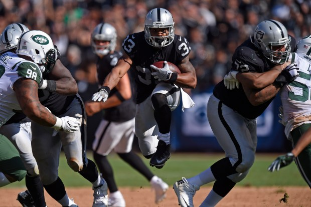 Oakland Raiders' DeAndre Washington (33) runs for yardage against the New York Jets in the fourth quarter of their NFL game at the Oakland Coliseum in Oakland, Calif. on Sunday, Sept. 17, 2017. The Oakland Raiders defeated the New York Jets 45-20. (Jose Carlos Fajardo/Bay Area News Group)