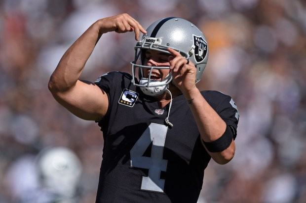 Oakland Raiders quarterback Derek Carr (4) is all smiles after teammate Jalen Richard (30) scores a touchdown in the fourth quarter of their NFL game at the Oakland Coliseum in Oakland, Calif. on Sunday, Sept. 17, 2017. The Oakland Raiders defeated the New York Jets 45-20. (Jose Carlos Fajardo/Bay Area News Group)