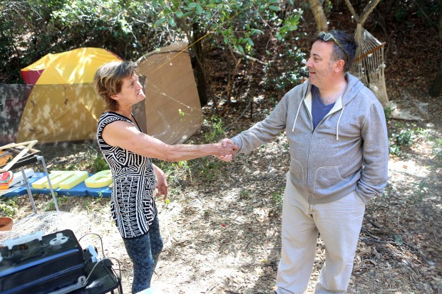 Los Gatos resident John Whitney meets up with Cassie Fuqua, who lives in an encampment that borders his downtown Los Gatos property. Whitney noted the area looks much cleaner than in the past but still worries about possible fire danger from barbeques and campfires in the tinder dry area. (George Sakkestad/Staff Photographer)