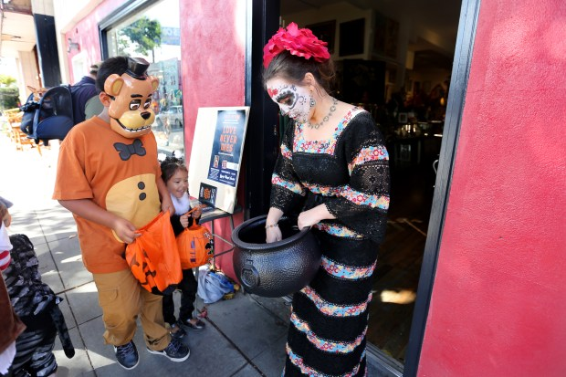 Heather Warden, right, owner of Gypsy Road Studio, hands out candies to Halloween enthusiasts during the 30th Annual Piedmont Avenue Merchant Association's Halloween Celebration in Oakland, Calif., on Saturday, Oct. 29, 2016. The festivities began with a parade, followed by trick-or-treating at businesses on Piedmont Avenue. The Mountain View Cemetery hosted the annual Pumpkin Patch Meadow, jumpers, food trucks, among other things. The Chapel of the Chimes also featured free movies. (Ray Chavez/Bay Area News Group)
