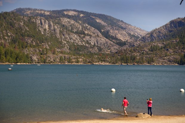 Brian Phipps and Barbara Patterson, of San Jose, enjoy an autumn day atPinecrest Lake with their dog Shasta. In the summer months, this lake and its shoreline are filled with people, but fall brings peace to this mountainside region. (Courtesy of Dino Vournas)