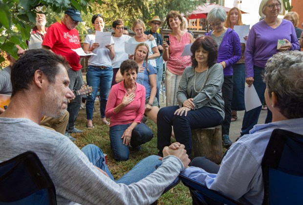 "Guests sing ""You've got a Friend"" to Jil Finnegan, right, and her husband, Geoff Protz, left, during a farewell party at their home in Oakland, California on Saturday, September 16, 2017. Finnegan, who has cancer, has opted to die under California's right-to-die law on her wedding anniversary. The party also served to celebrate the birthday of her husband Geoff Protz. (LiPo Ching/Bay Area News Group)"