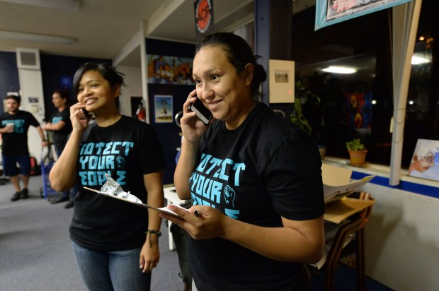 Cecilia Chavez, right, of San Jose, and Charisse Domingo, left, of San Jose, make last second phone calls to people signed up to meet them at De-Bug headquarters in San Jose, Calif., on Friday, Sept. 1, 2017. A group from the social justice group Silicon Valley De-Bug and supporters gathered early in the morning to board a bus to make the trip to Sacramento to attend a public hearing on proposed regulations regarding Prop. 57. Governor Jerry Brown's proposed Public Safety and Rehabilitation Act was approved by voters in 2016. De-Bug supports the regulations. (Dan Honda/Bay Area News Group)