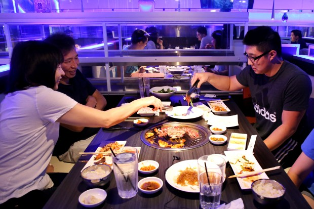 Cathy Lin, left, her husband Chun Hou and their son Michael Hou, 22, put their food on a grill after is was delivered by a robot server along a track system at the Gen Korean BBQ House in Fremont, Calif., on Saturday, Sept. 2, 2017. (Ray Chavez/Bay Area News Group)