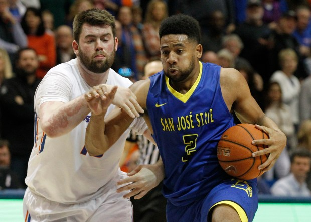 San Jose State's Gary Williams Jr. (2) moves the ball past Boise State's Nick Duncan during the second half of an NCAA college basketball game in Boise, Idaho, Saturday, Feb. 25, 2017. Williams has sued former head coach Gary Wojcik and assistant coach Tyler Ojanen for allegedly homophobic taunts and other discriminatory behavior. (AP Photo/Otto Kitsinger)