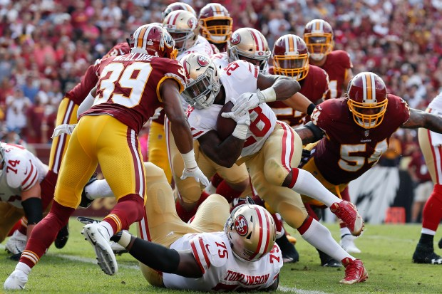 San Francisco 49ers running back Carlos Hyde (28) carries the ball into the end zone for a touchdown under pressure from Washington Redskins running back Keith Marshall (39) during the first half of an NFL football game in Landover, Md., Sunday, Oct. 15, 2017. (AP Photo/Alex Brandon)