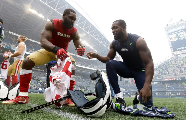 Seattle Seahawks strong safety Kam Chancellor, right, trades jerseys with San Francisco 49ers middle linebacker NaVorro Bowman, left, after a Week 2 meeting the Seahawks won 12-9. Chancellor won't play Sunday because of a neck issue while Bowman will play across the Bay with the Raiders. (AP Photo/Elaine Thompson)