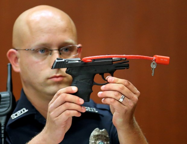 File photograph: A police holds up the gun that was used to kill Trayvon Martin, while testifying in the George Zimmerman trial in Sanford, Fla. (AP Photo/Orlando Sentinel, Joe Burbank, Pool, File)