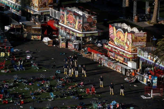 Investigators work at a festival grounds across the street from the Mandalay Bay Resort and Casino on Tuesday, Oct. 3, 2017, in Las Vegas. (AP Photo/Marcio Jose Sanchez)