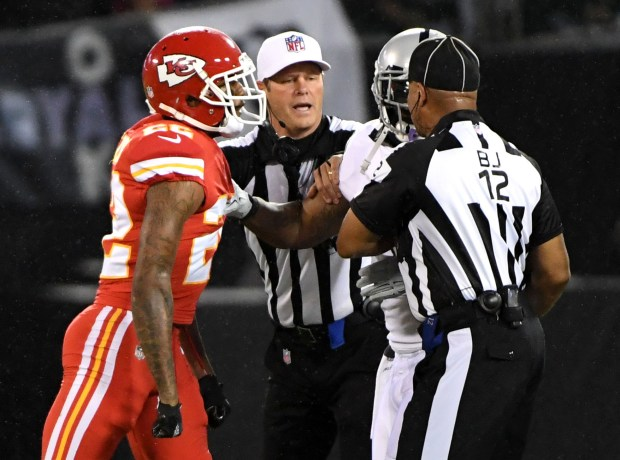 Referee Craig Wrolstad, (4) , center, and back judge Greg Steed, (12), right, break up Kansas City Chiefs' Marcus Peters (22) and Oakland Raiders' Marshawn Lynch (24) in the second quarter of their NFL game at the Coliseum in Oakland, Calif. on Thursday, Oct. 19, 2017. Lynch was ejected from the game because of contact with an official. (Doug Duran/Bay Area News Group)