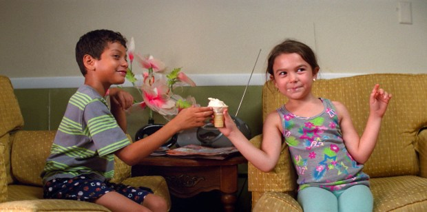 """This image released by A24 shows Christopher Rivera, left, and Brooklynn Prince in a scene from """"The Florida Project."""" (A24 via AP)"""