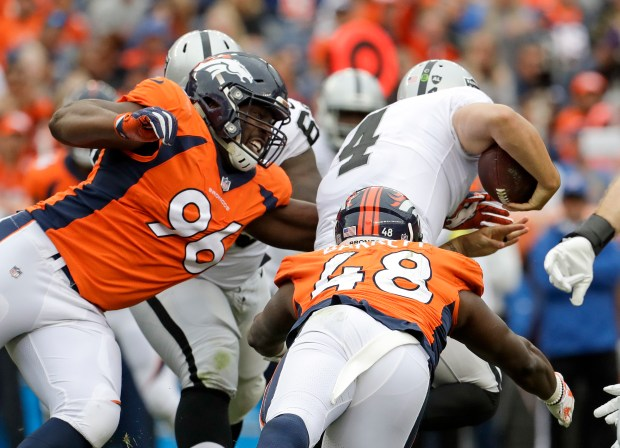 Oakland Raiders quarterback Derek Carr (4) is tackled by Denver Broncos defensive end Shelby Harris, left, and outside linebacker Shaquil Barrett during the second half of an NFL football game Sunday, Oct. 1, 2017, in Denver. Carr was injured on the play. (AP Photo/Joe Mahoney)