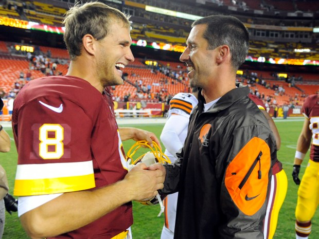FILE - In this Aug. 18, 2014, file photo, Washington Redskins quarterback Kirk Cousins (8) talks with then-Cleveland Browns offensive coordinator Kyle Shanahan after an NFL preseason football game, in Landover, Md. Facing the first offensive coordinator who believed in him in now San Francisco 49ers coach Kyle Shanahan, Cousins is still evolving and improving as a quarterback for the Redskins. (AP Photo/Richard Lipski, File)