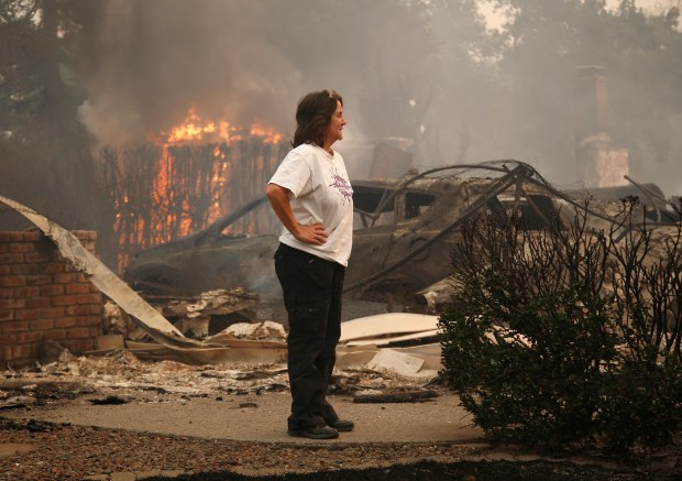 Sandy Champie surveys the destruction of her mother's home, behind her, one that she grew up in, on Aaron Drive, in Santa Rosa, Calif. on Monday, Oct. 9, 2017. Her parents purchased the home in the 1970s. (Nhat V. Meyer/Bay Area News Group)