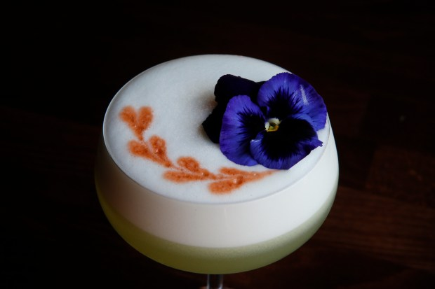 A Banaras Sour, a cocktail made of Broker's Gin, basil, cucumber and Chartreuse adorned with a pansy, is served at Rooh restaurant, Tuesday, October 31, 2017, in San Francisco, California. (Karl Mondon/ Bay Area News Group)