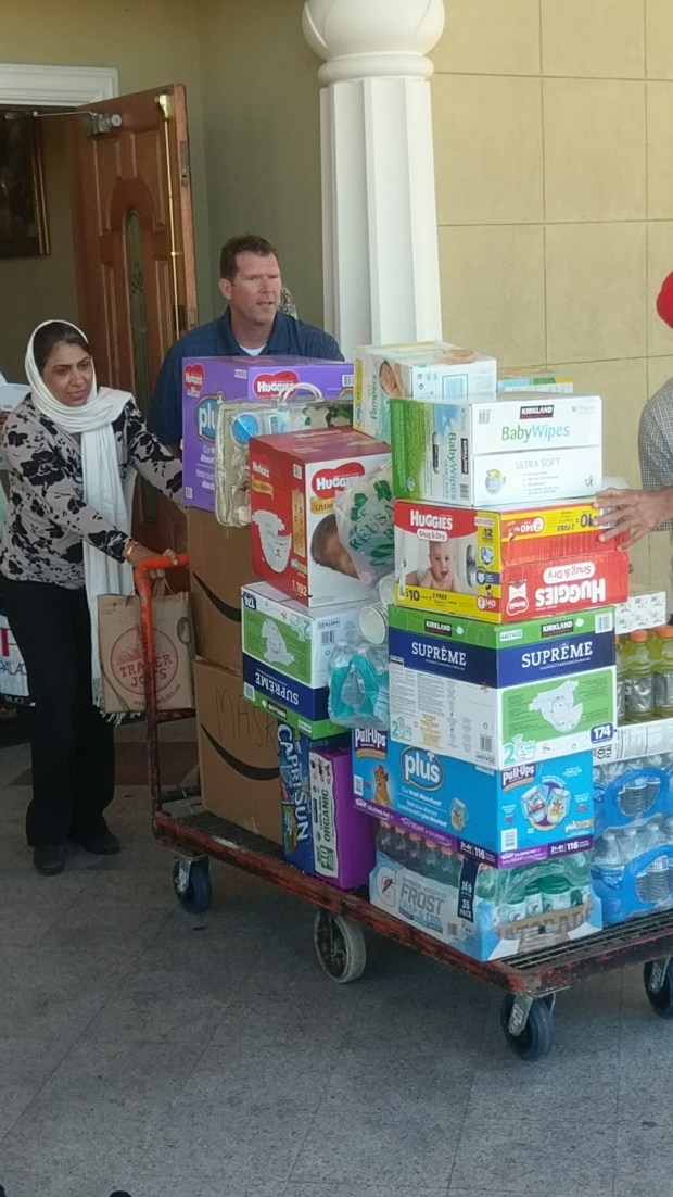 Greg Connolly, board member of the San Jose Police Officers' Association, works with members of the Sikh Gurdwara of San Jose to load an 18-wheeler full of donated supplies that will be transported to help fire-affected communities in Sonoma County on Oct. 24, 2017.