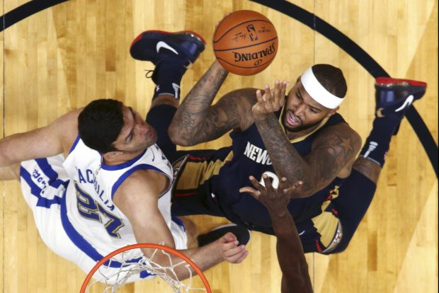 New Orleans Pelicans forward DeMarcus Cousins ,right, goes to the basket against Golden State Warriors center Zaza Pachulia (27) and forward Draymond Green in the first half of an NBA basketball game in New Orleans, Friday, Oct. 20, 2017. (AP Photo/Gerald Herbert)