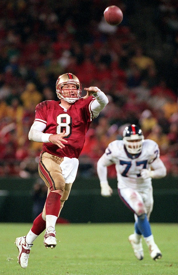 49ers QB Steve Young throws on the run during 31-7 win over the New York Giants at 3COM Park Monday 11/30/98. Young ran for 62 yards and threw for two touchdowns. (Eddie Ledesma/Bay Area News Group)