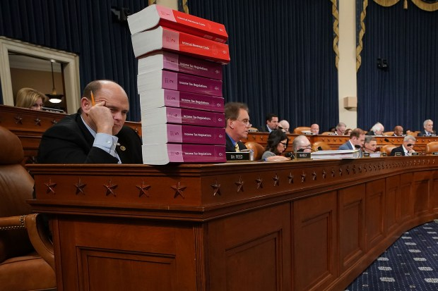 House Ways and Means Committee member Rep. Tom Reed (R-NY) keeps a stack of books that document the current federal tax code and related regulations on his desk during the first markup of the proposed GOP tax reform legislation in the Longworth House Office Building on Capitol Hill November 6, 2017 in Washington, DC. President Donald Trump said that he wants to sign new tax cuts into law before the end of the year. (Photo by Chip Somodevilla/Getty Images)