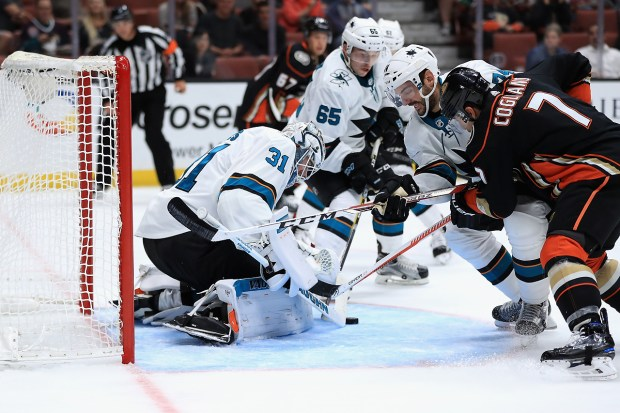 Martin Jones #31, Dylan DeMelo #74 and Danny O'Regan #65 of the San Jose Sharks defend against Andrew Cogliano #7 of the Anaheim Ducks during the third period of a preseason game at Honda Center on September 28, 2017 in Anaheim, California. (Sean M. Haffey/Getty Images)