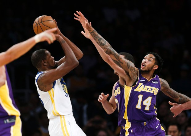 Golden State Warriors forward Kevin Durant, left, shoots under pressured from Los Angeles Lakers forwards Brandon Ingram, right, and Larry Nance Jr. during the first half of an NBA basketball game Wednesday, Nov. 29, 2017, in Los Angeles. (AP Photo/Ringo H.W. Chiu)