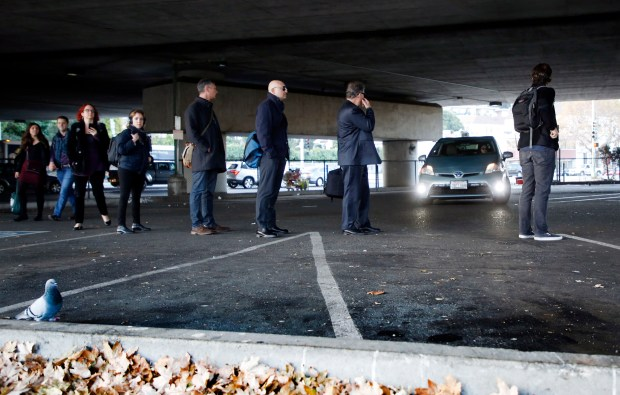 Commuters line up at a casual carpool pick-up site under the 580 freeway in Oakland, Calif., on Thursday, Nov. 2, 2017. (Laura A. Oda/Bay Area News Group)