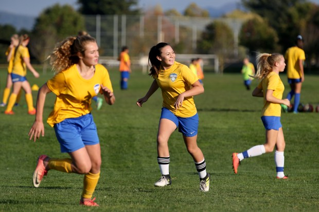 Santa Rosa Soccer Club player Emi Watanabe, 12, center, smiles during practice at A Place to Play fields in Santa Rosa, Calif., on Thursday, Nov. 2, 2017. The club with boys and girls teams ranging in ages from 7 to 18 are practicing at the temporary field after their home field was destroyed in the recent North Bay wildfires. Watanabe and her family are one of 50 families from the club to lose homes in the wildfires. (Anda Chu/Bay Area News Group)