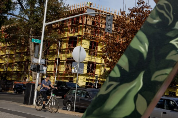 A bicyclist rides near a housing construction project on Nov. 7, 2017, in Sacramento. The Sacramento area is seeing a wave of Bay Area transplants drawn to its relative affordability as prices soar in Oakland, San Jose and San Francisco.(Dai Sugano/Bay Area News Group)