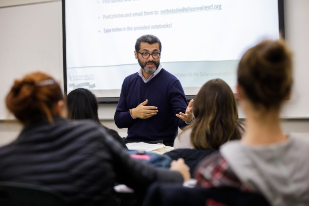 Mauricio Palma, director of initiatives and special projects for the Silicon Valley Community Foundation and an instructor at Cañada College, helps students prepare for an upcoming event, On the Table, a community-wide conversation about the region's housing crisis, on Nov. 9, 2017, at Cañada College in Redwood City. (Dai Sugano/Bay Area News Group)