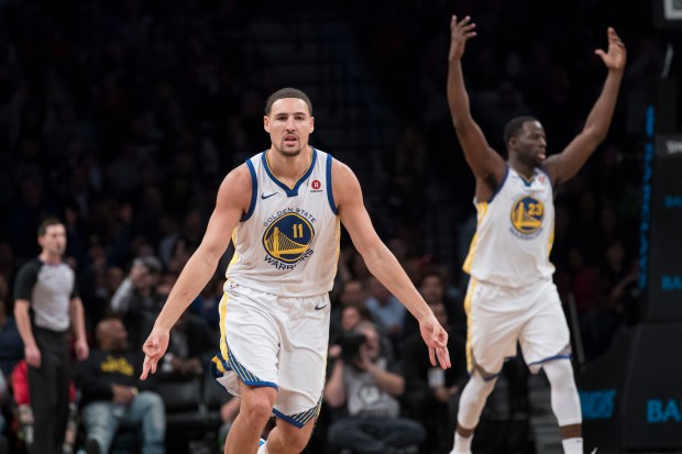 Golden State Warriors guard Klay Thompson (11) and forward Draymond Green (23) reacts after Thompson scored a three-point basket during the final minutes of the second half of an NBA basketball game against the Brooklyn Nets, Sunday, Nov. 19, 2017, in New York. (AP Photo/Mary Altaffer)