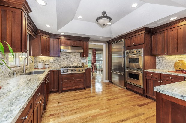The home's kitchen is fully remodeled with abundant counter space, soft-close custom cherry cabinets, granite slab counters and stainless steel appliances.