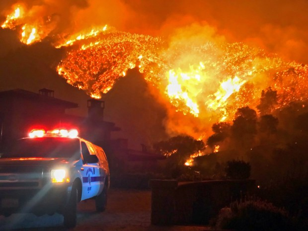 In this photo provided by the Santa Barbara County Fire Department, fire burns canyons and ridges above Bella Vista Drive near Romero Canyon as the fight to contain a wildfire continues in Montecito, Calif., Tuesday, Dec. 12, 2017. The fifth-largest wildfire in California history expanded Tuesday, ripping through dry brush atop a coastal ridge while crews struggled to keep flames from roaring down into neighborhoods amid fears of renewed winds. (Mike Eliason/Santa Barbara County Fire Department via AP)