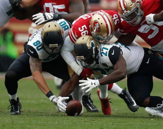 Jacksonville Jaguars' Leonard Fournette (27) recovers his fumble against San Francisco 49ers' Reuben Foster (56) in the second quarter of their NFL game at Levi's Stadium in Santa Clara, Calif., on Sunday, Dec. 24, 2017. (Nhat V. Meyer/Bay Area News Group)