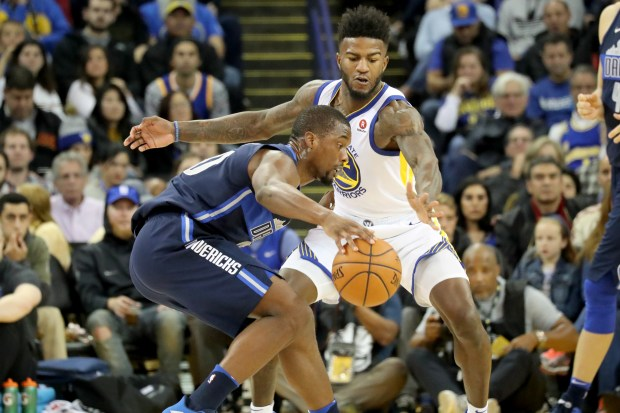 Dallas Mavericks' Harrison Barne (40) dribbles against Golden State Warriors' Jordan Bell (2) n the first half at Oracle Arena in Oakland, Calif., on Thursday, Dec. 14, 2017. (Ray Chavez/Bay Area News Group)
