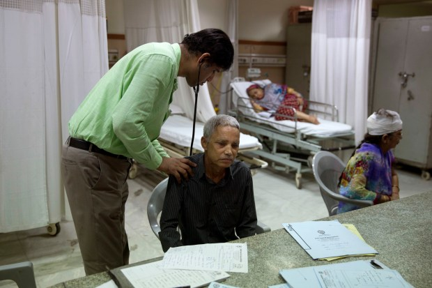"""In this Oct. 23, 2017 photo, a doctor examines Jagat Singh, 59, at the Delhi Heart and Lung Institute in New Delhi, India. Over the past decade, pollution has sharply increased in New Delhi with more cars, a construction boom and small factories on the outskirts that burn dirty fossil fuels with little oversight. In October and November, for the second year in a row, city air pollution levels were so high they couldn't be measured, and newspapers ran headlines warning of an """"Airpocalypse."""" About 1.1 million Indians die prematurely as a result of outdoor pollution every year. (AP Photo/Tsering Topgyal)"""