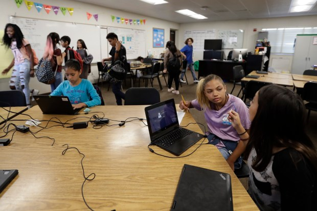 In this Oct. 24, 2017, photo, Shawnni Wade, 12, second from right, talks with a friend at Perkins Elementary School in San Diego. Perkins has a playground with a panoramic view of sleek high-rises and the shiny dome of the city's new central library; it also has a student body that is more than a quarter homeless, up from 4 percent three years ago. (AP Photo/Gregory Bull)