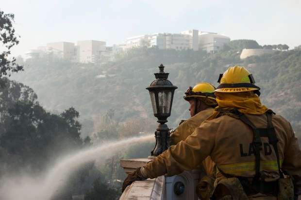 Los Angeles City firefighters Tanner Keeler, left, and Francisco Martinez protect a home on Bel Terrace as firefighters battle the Skirball Fire in Bel-Air on Wednesday, Dec. 06, 2017. (Photo by Ed Crisostomo, Los Angeles Daily News/SCNG)