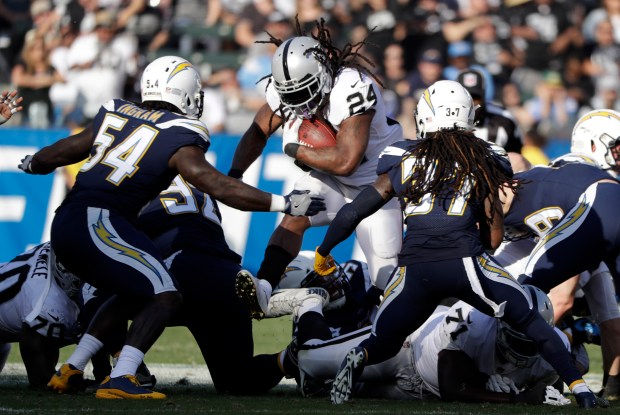 Oakland Raiders running back Marshawn Lynch, above, runs up the middle during the first half of an NFL football game against the Los Angeles Chargers, Sunday, Dec. 31, 2017, in Carson, Calif. (AP Photo/Alex Gallardo)