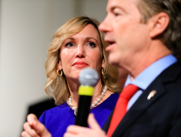 "FILE - In this Feb. 1, 2016, file photo, Kelley Paul, wife of Republican Sen. Rand Paul, R-Ky, watches him speak to supporters during a caucus night rally at the Scottish Rite Consistory in Des Moines, Iowa. Kelley Paul writes in an essay published by CNN on Nov. 22, 2017, that her husband hasn't taken a single breath without pain since what she calls ""a deliberate, blindside attack"" by the family's Kentucky neighbor earlier this month. (AP Photo/Nati Harnik, File)"