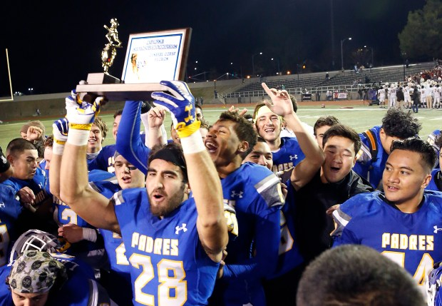Serra's Shane Villaroman (28) holds up the winning trophy in the CCS Open Division II championship game on Saturday, Dec. 2, 2017, in San Jose, Calif. Serra won 31-30. (Tony Avelar/Bay Area News Group)